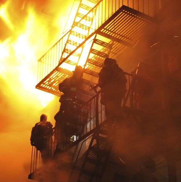 Firefighters stand on a fire escape of a burning building in the Brooklyn area of New York (AP)