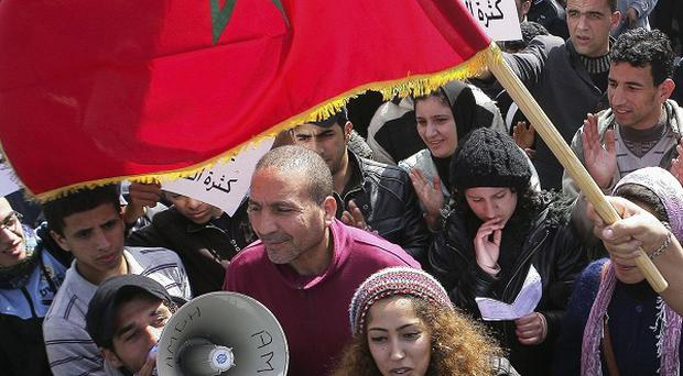 Protesters march during a protest and wave the Moroccan flag in Rabat (AP)
