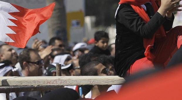 Bahraini anti-government protesters chant and wave Bahraini flags at the Pearl roundabout in Manama (AP)