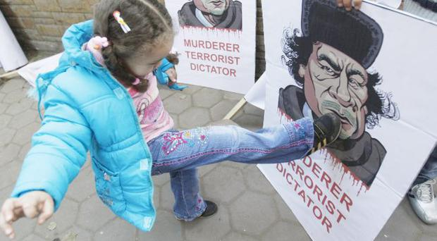A Libyan girl kicks a poster of Libyan Leader Moammar Gadhafi, during a protest in front of the Libyan embassy in Cairo, Egypt, Monday Feb. 21, 2011.