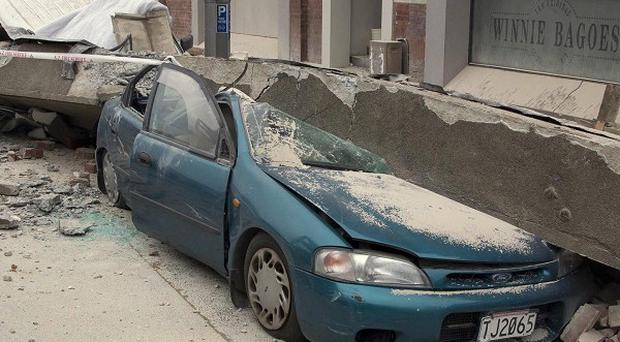 A car is crushed by a beam in central Christchurch after a powerful earthquake hit (AP)
