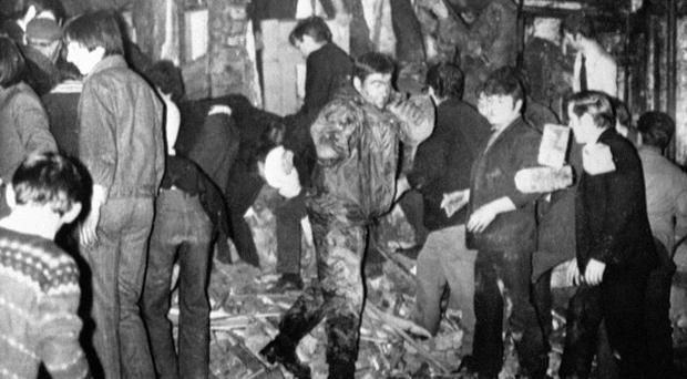 Rescuers, soldiers and civilians, digging with bare hands in the still smoking rubble of McGurk's bar