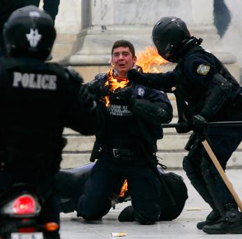 ATHENS, GREECE - FEBRUARY 23: A police officer is helped from his motorcycle after being hit by a petrol bomb as police in full riot gear clash with protesters in front of parliament in on February 23,2011 in Athens, Greece. Greek police clashed with protesters as workers marched on parliament protesting against austerity measures introduced to help the country manage it's huge national debt. (Photo by Milos Bicanski/ Getty Images) *** BESTPIX ***