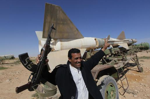 A Libyan popular defence committee, holds his AK-47 as he flashes V sign in front an anti-aircraft missile at an abandoned Libyan military base near Tobruk, Libya, on Wednesday, Feb.23, 201