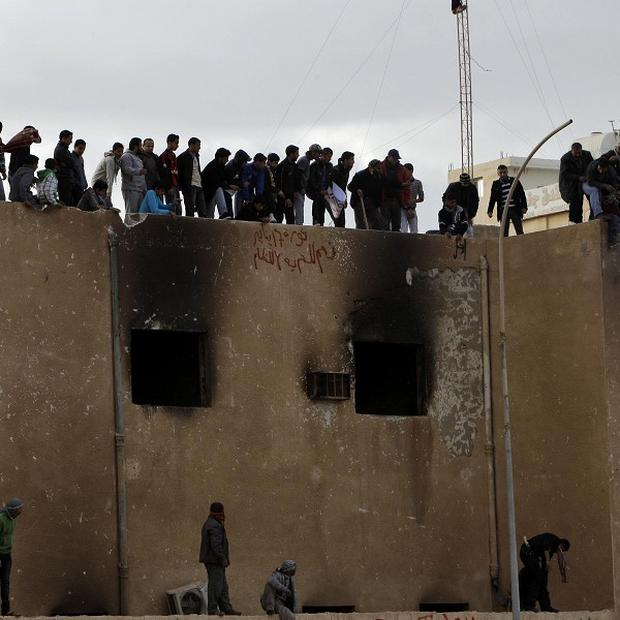 Libyan protesters stand atop a damaged police station as they burn an effigy of Libyan leader Moammar Gaddafi (AP)