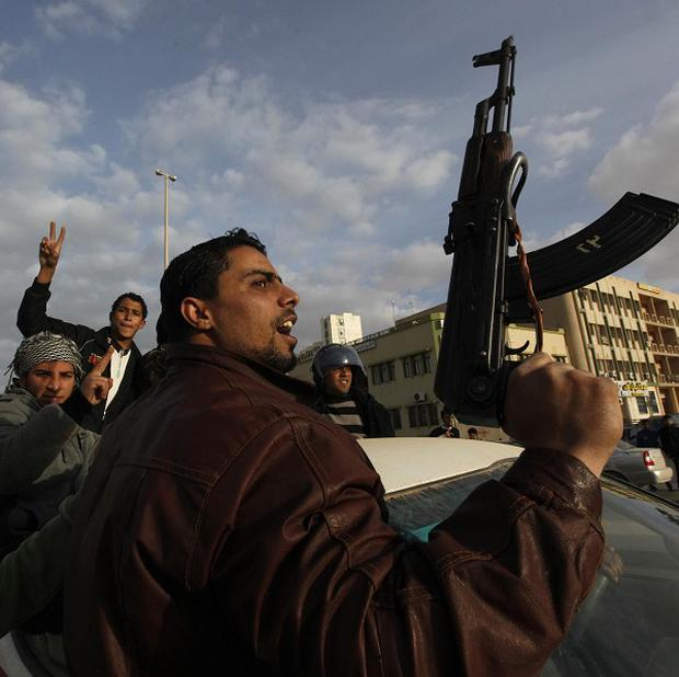 A protester holds a weapon as he shouts slogans against Libyan leader Muammar Gaddafi during a demonstration in Tobruk (AP)