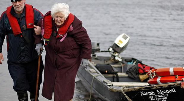 Bridgie O'Malley, 83, is helped by her son Joe after casting her vote on the island of Inishbiggle