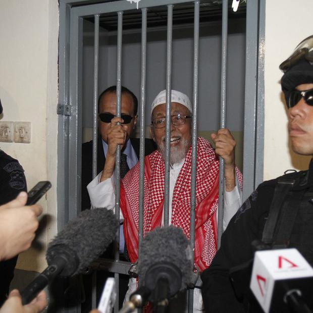 Radical Muslim cleric Abu Bakar Bashir speaks to the media from behind bars before the start of his trial in Indonesia (AP)