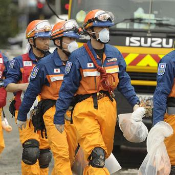 Personnel from Japan Disaster Relief team move through the destroyed CTV building in Christchurch, New Zealand (AP)
