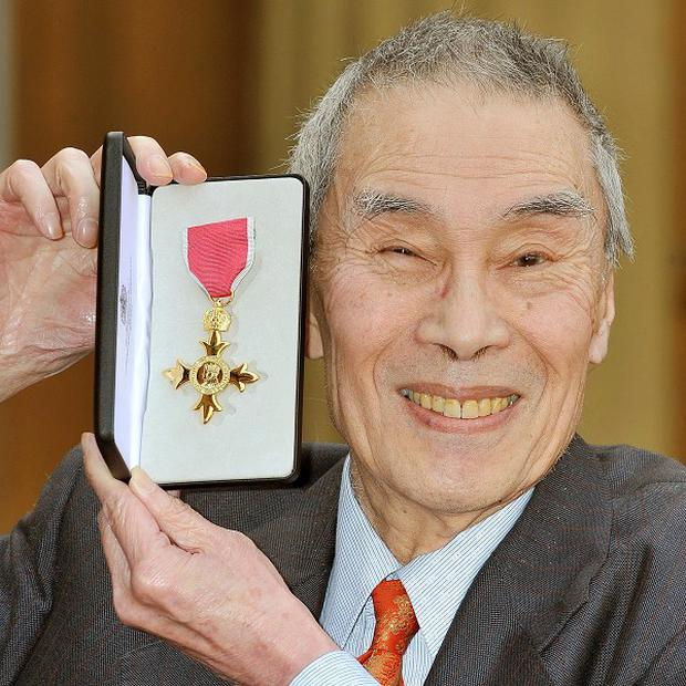Burt Kwouk proudly holds his Officer of the British Empire (OBE)