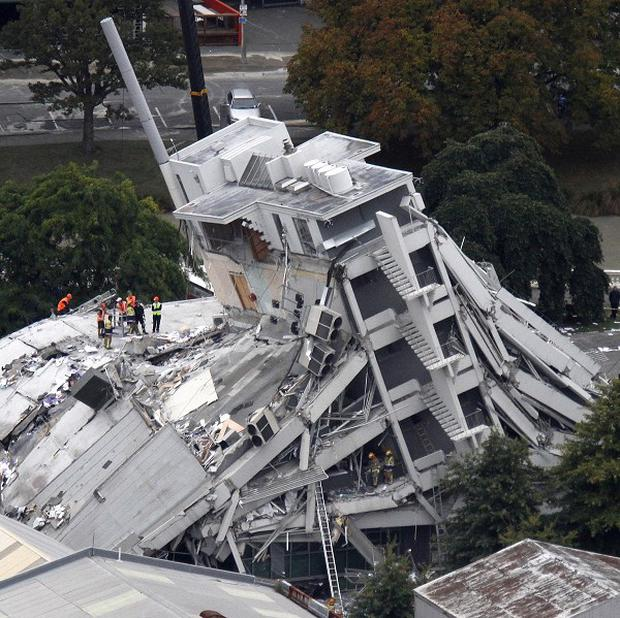 Rescue workers climb on to the collapsed Pyne Gould Guinness building in central Christchurch (AP)