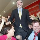 Sinn Fein President Gerry Adams is lifted by supporters, after being elected TD, in Co Louth during the Irish general election.