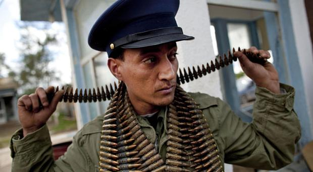A Libyan rebel that is a member of forces against Libyan leader Moammar Gadhafi wears ammunition outside a military base in Benghazi, eastern Libya, Monday, Feb. 28, 2011. (AP Photo/Kevin Frayer)