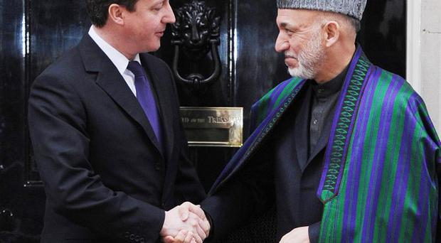Prime Minister David Cameron greets Afghan President Hamid Karzai in Downing Street