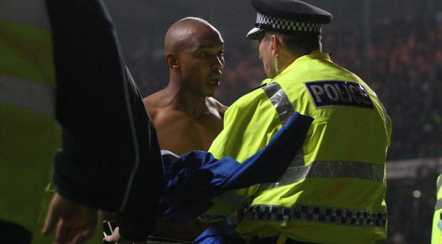 Rangers' El Hadji Diouf tries to throw his jersey to the fans and is stopped by a policeman after the Scottish Cup Fifth Round Replay at the Celtic Park, Glasgow