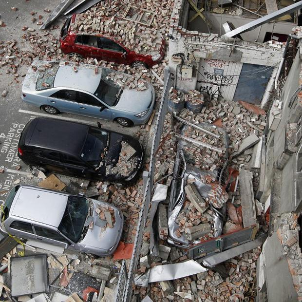 Cars lie under rubble in the central business district in Christchurch, New Zealand (AP)