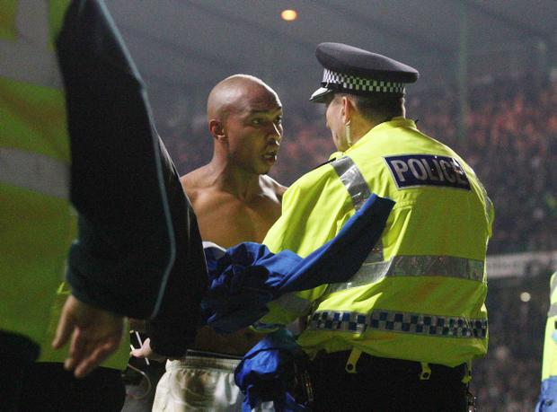 Rangers El Hadji Diouf tries to throw his jersey to the fans and is stopped by a policeman after the Scottish Cup Fifth Round Replay at Celtic Park, Glasgow