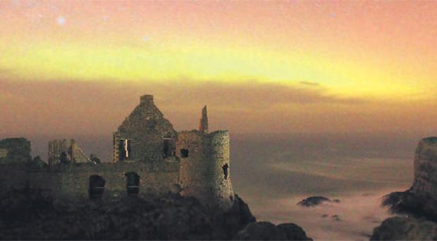 The aurora borealis dancing in the skies above Dunluce Castle