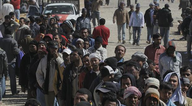 People displaced from the violence in Libya await aid handouts at a refugee camp in Ras Ajdir, Tunisia (AP)