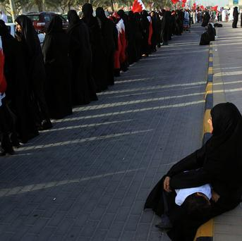 Bahraini anti-government protesters form a human chain stretching around Manama (AP)