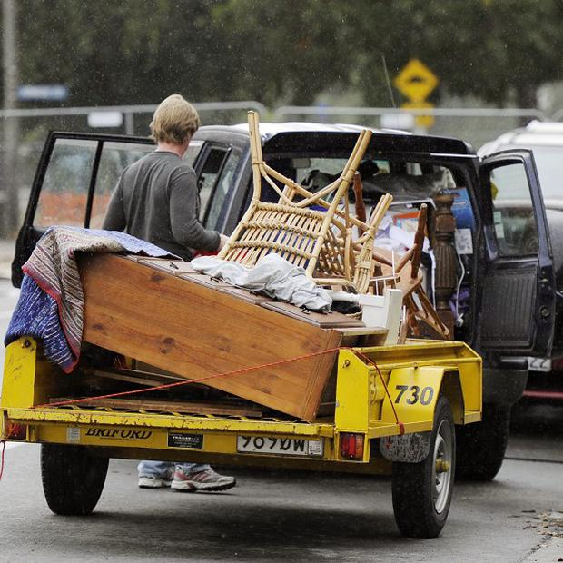 Residents prepare to transport furniture and household goods from homes in Christchurch, New Zealand, after police cordons are relaxed (AP)