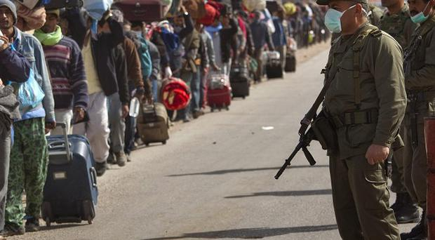 Tunisian soldiers stand guard as Bangladeshi workers fleeing Libya walk with their belongings (AP)
