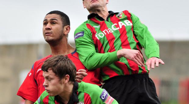 Colin Nixon gets up above Marc Mukendi and Glentoran team mate Johnny Black to win the ball