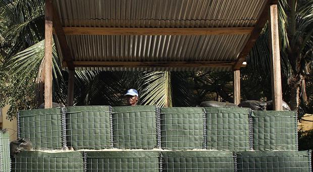 A soldier stands guard outside an Abidjan hotel where Alassane Ouattara is under 24-hour UN protection (AP)