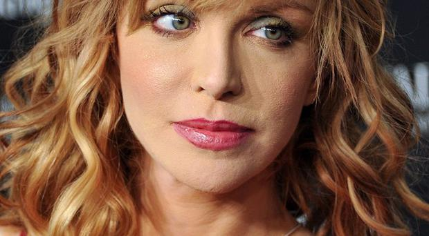 Courtney Love has paid out over comments she made about a designer on Twitter (AP)