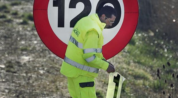 A motorway maintenance worker prepares to change a sign to reflect the new speed limit (AP)