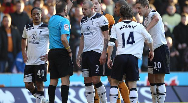 Referee Mark Halsey prepares to give Tottenham's Alan Hutton a yellow card at Wolverhampton on Sunday