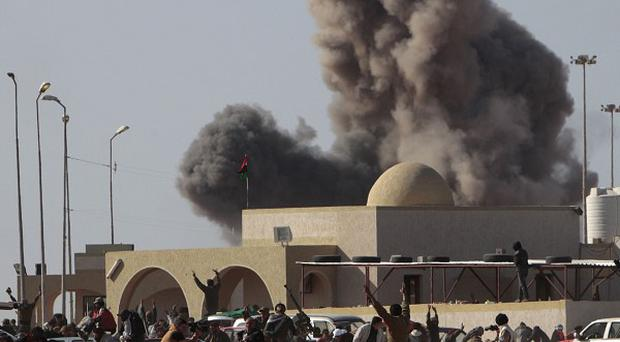 Anti-Gaddafi rebels react following an air strike by Libyan war planes near a checkpoint in Ras Lanuf (AP)