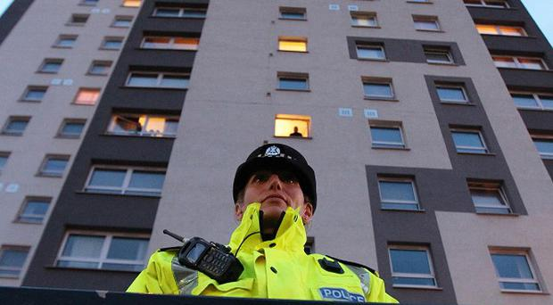 A police officer outside flats in Whiteinch, Glasgow, where police searched an address in connection with a man held over the Stockholm bombing