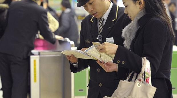 Japan Railway Sendai Station staff help stranded bullet train passengers after the service was suspended (Kyodo News)
