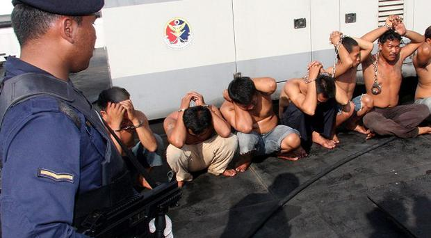 Malaysian Maritime Enforcement Agency enforcement officers keep watch on detained Indonesian pirates in Johor (AP)