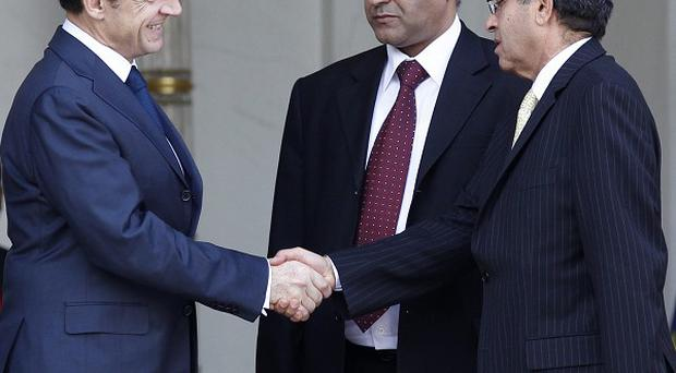 French President Nicolas Sarkozy (left) shakes hands with representatives of the newly-formed council based in the Libyan city of Benghazi (AP)