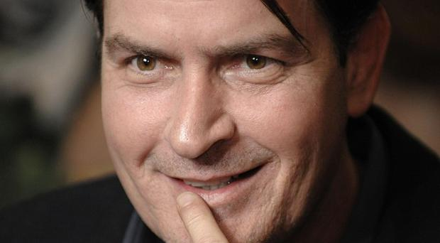 Charlie Sheen is suing Warner Bros over the halting of production of Two and a Half Men (AP)
