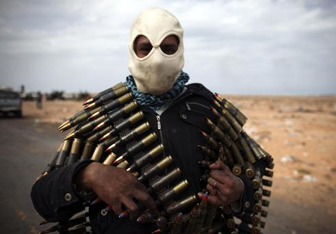 A Libyan volunteer carries ammunition on the outskirts of the eastern town of Ras Lanouf, Libya, Thursday, March 10, 2011