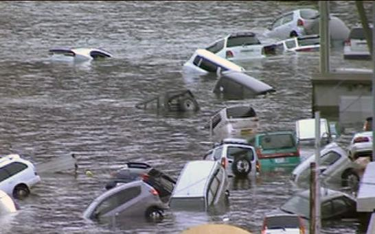 In this image made off Japan's NHK TV video footage, vehicles are washed away by tsunami in coastal area in eastern Japan