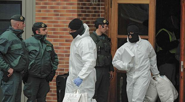 Spanish Civil Guards leave a building after the arrested of an alleged member of the Basque separatist armed group ETA (AP)
