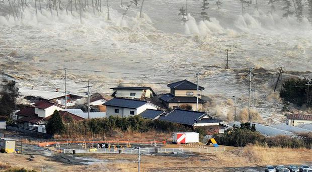 Waves from the tsunami hit homes after a powerful earthquake in Natori, Miyagi prefecture, Japan (AP Photo/Kyodo News)