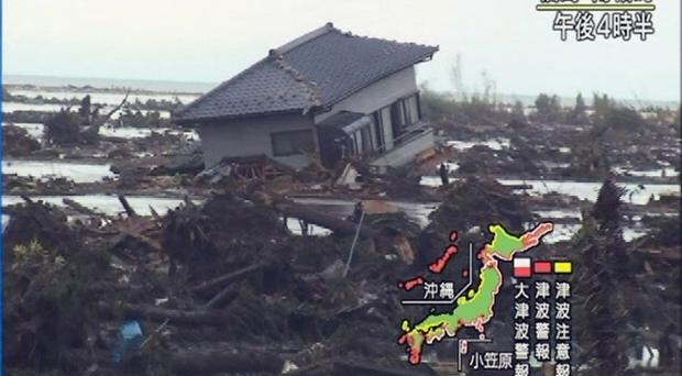 In this image made from Japan's NHK television, a house is sticks out from scattered debris as the area is submerged in Minami Soma, Fukushima prefecture (state), Friday, March 11, 2011 after a ferocious tsunami unleashed by Japan's biggest recorded earthquake slammed into its eastern coasts
