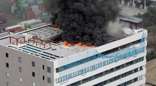 Black smoke raises from a building during a fire in Tokyo after one of the largest earthquakes on record slammed Japan's eastern coasts Friday, March 11, 2011