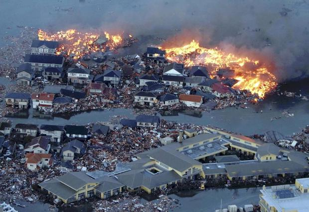 Houses are in flames while the Natori river is flooded over the surrounding area by tsunami tidal waves in Natori city, Miyagi Prefecture, northern Japan, March 11, 2011, after strong earthquakes hit the area