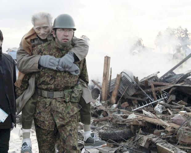 An elderly man is carried by a Self-Defense Force member in the tsunami-torn Natori city, Miyagi Prefecture, northern Japan, Saturday morning, March 12, 2011, one day after strong earthquakes hit the area