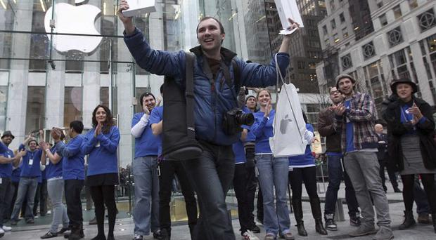 Alex Shumilov of Moscow was the first customer to walk out of the Apple store on Fifth Avenue in New York after purchasing two iPad 2s (AP)