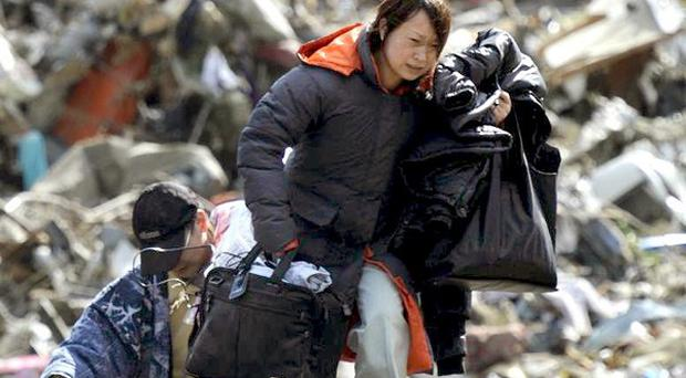 A woman carries belongings she collected from a house swept by a tsunami at Rikuzentakada (AP)