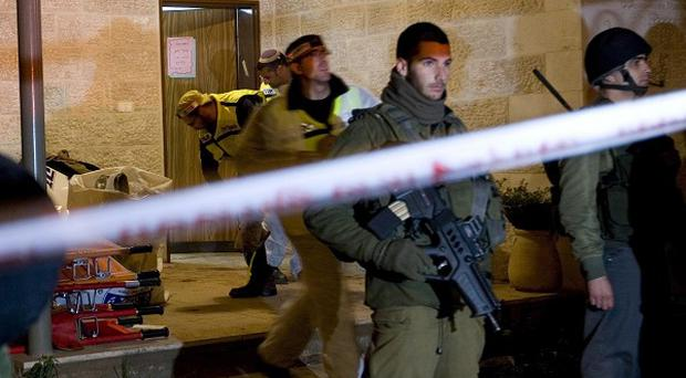 Israeli soldiers stand guard at the entrance to a home in the West Bank Jewish settlement of Itamar, where five people were killed (AP)