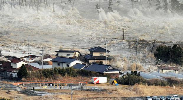 Waves from the tsunami hit homes after a powerful earthquake in Japan (AP Photo/Kyodo News)