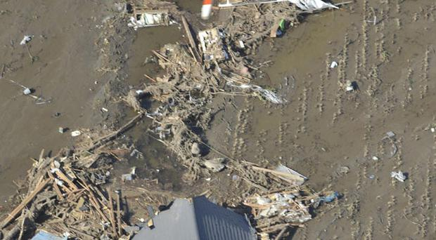 A helicopter from fire department searches over the debris of a destroyed house Monday, March 14, 2011 in Yamamoto, Miyagi Prefecture, Japan following Friday's massive earthquake and the ensuing tsunami. (AP Photo/Kyodo News) JAPAN OUT, MANDATORY CREDIT, NO SALES IN CHINA, HONG KONG, JAPAN, SOUTH KOREA AND FRANCE